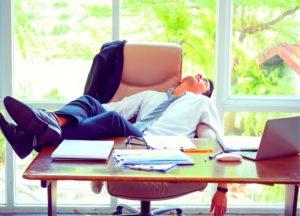 Lazy businessman asleep at his desk